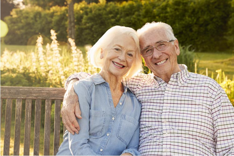 senior couple sitting on a bench outside pondering the benefits of a fixed bridge vs dentures for tooth loss
