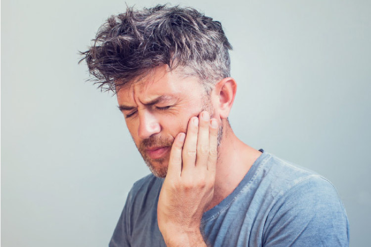 man holding his jaw and wincing with severe tooth pain