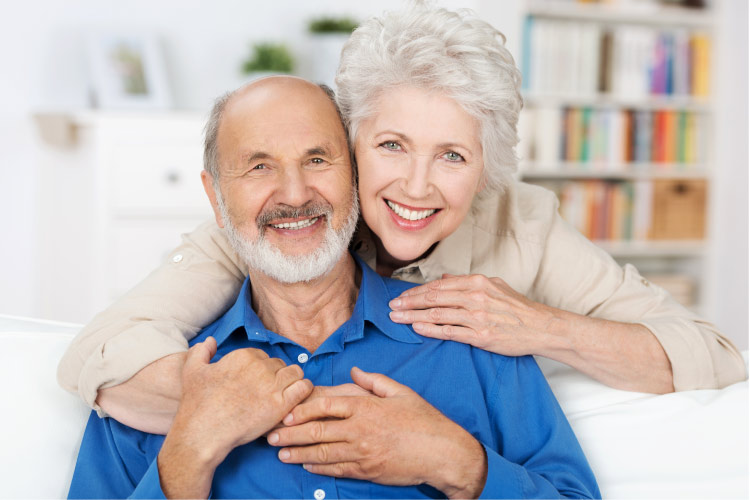 older couple hug and smile after learning about dental implants and bridges