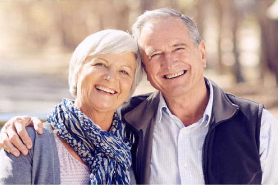 senior couple smile after receiving tooth replacements