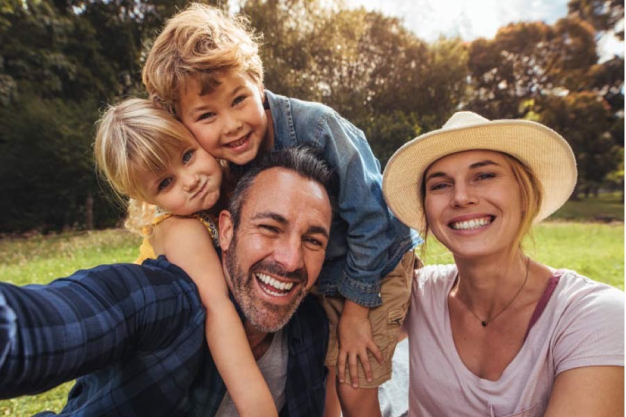 family of four hug and smile after scheduling a family dental appointment