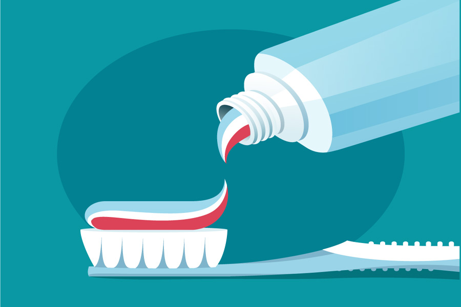 toothpaste being spread on a toothbrush