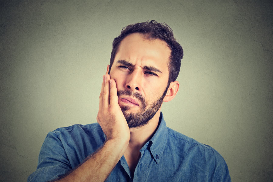 bearded man holds his jaw in pain from swollen gums